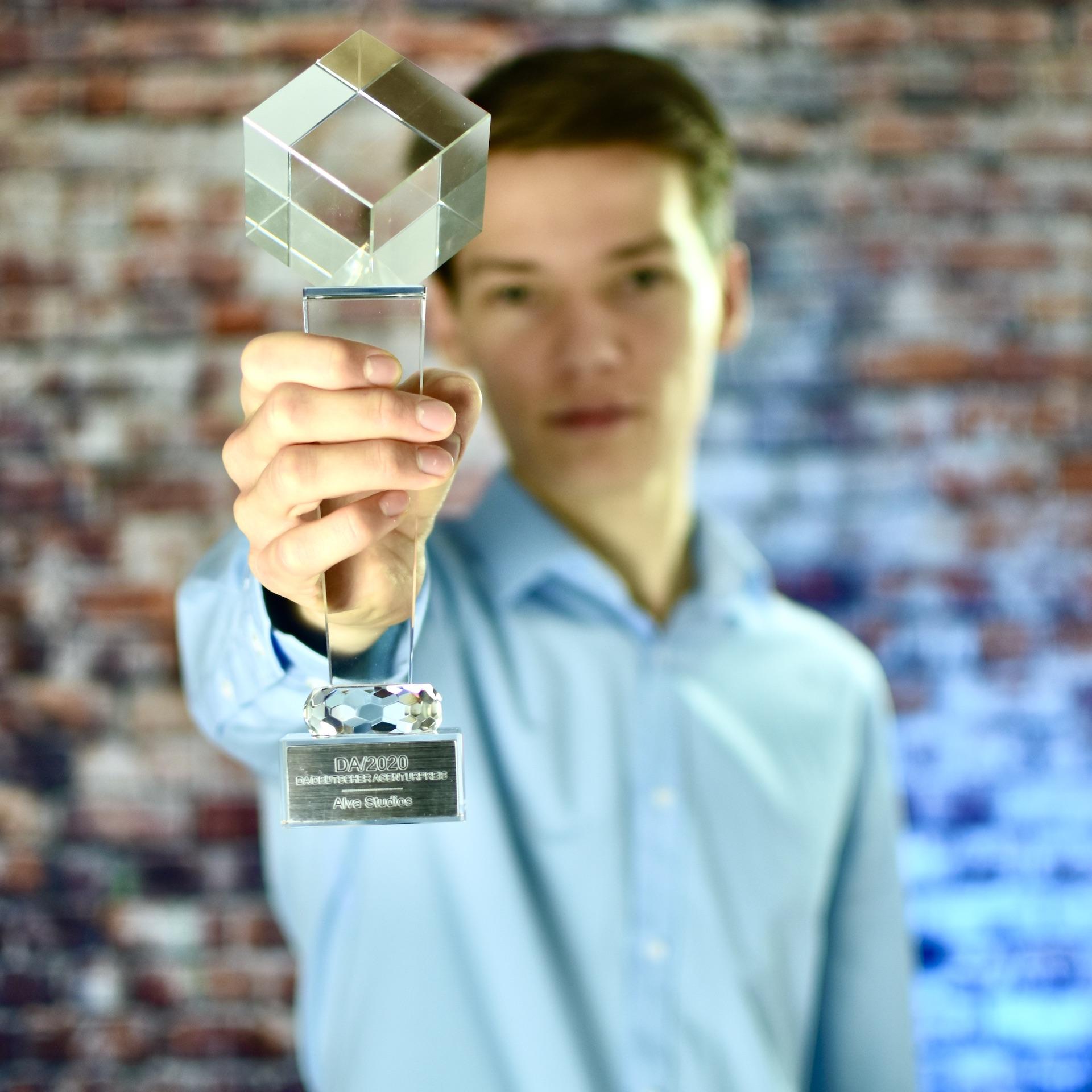 Nico Wolf hält den Pokal des Deutschen Agenturpreises für Alva Studios in der Kategorie TV-Spot